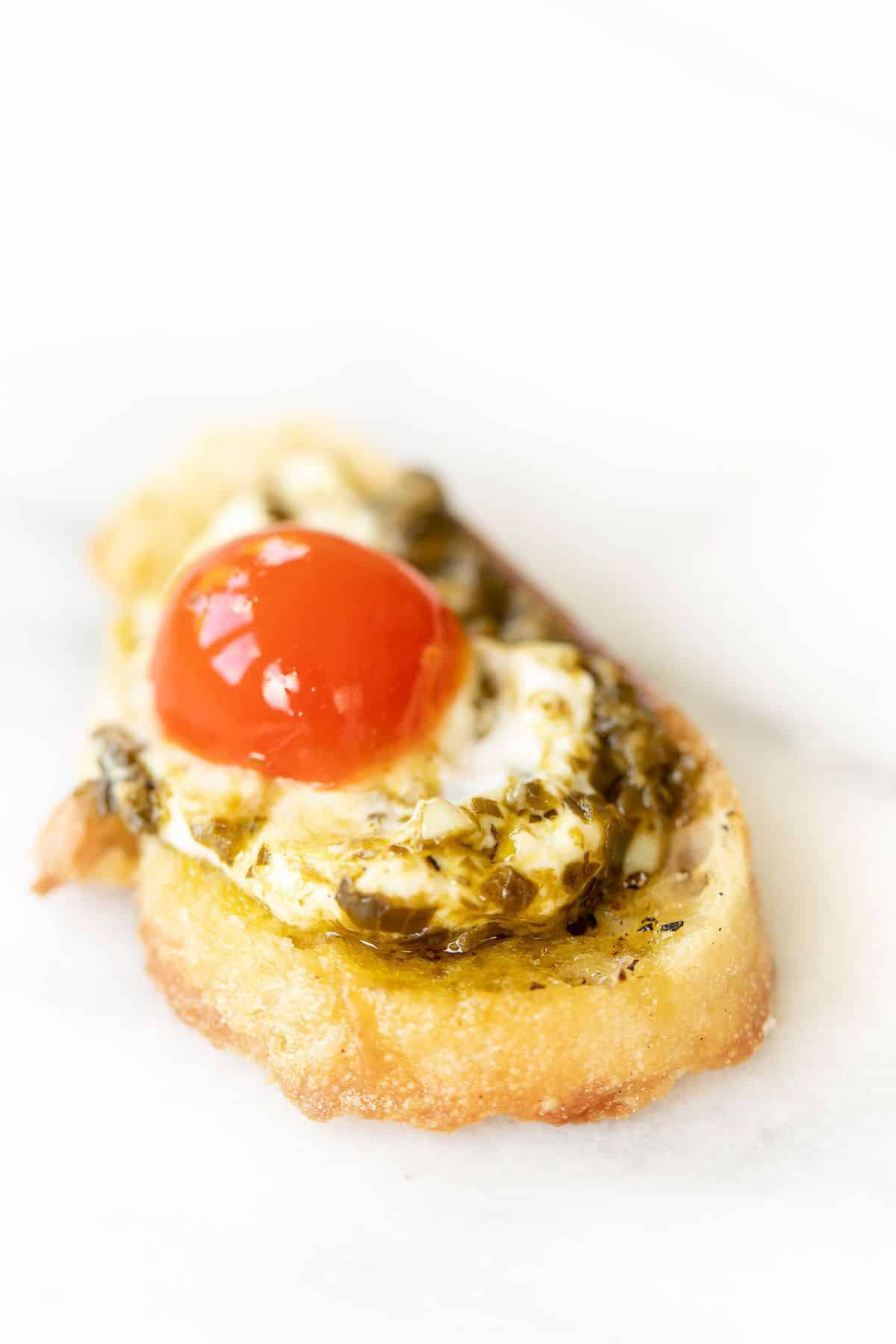 Marble surface, single slice of crostini topped with pesto cheese dip and a cherry tomato.