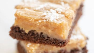 two slices peanut butter ooey gooey butter cake with powdered sugar on top