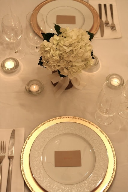 A table set with wine glasses, gold lined plates, and white flowers.