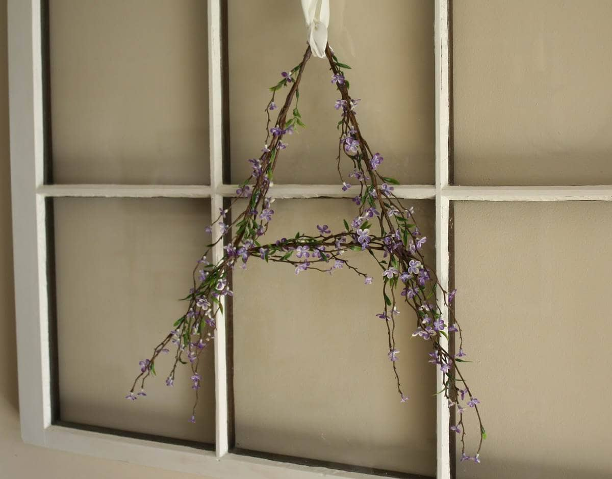 floral monogram wreath in shape of letter A hanging from window