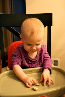 A baby sitting at a highchair.