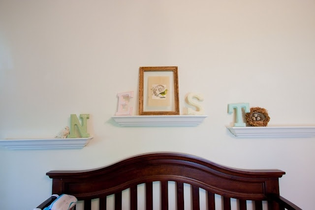 \'Nest\' on white shelves, above a brown, wooden crib.