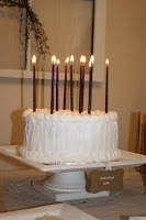 A white birthday cake with purple lit candles.