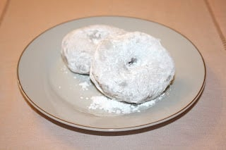Powdered donuts on a plate.