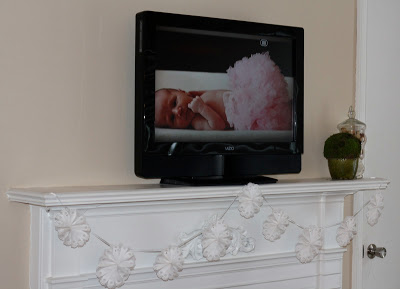 A framed picture of a baby in a pink tutu.
