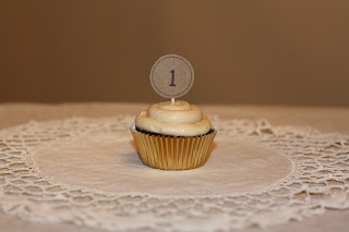 A cupcake in a gold wrapper, with a \'1\' sticking out of it.