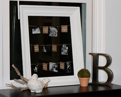 A picture frame with string and small pictures on it.