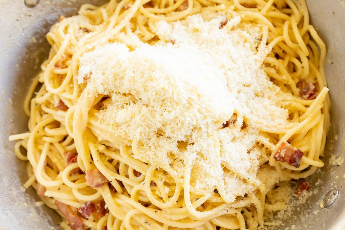 Looking into a silver pot filled with spaghetti carbonara topped with parmesan cheese