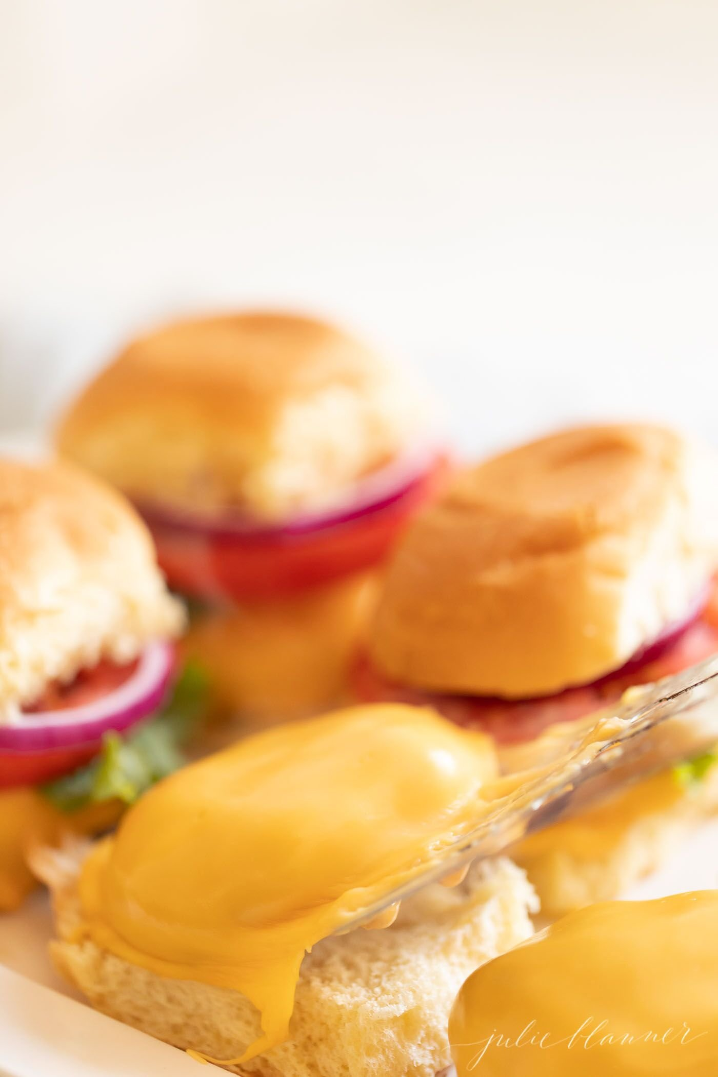 A group of 4 sliders, with patty covered in cheese in the foreground. #sliders.