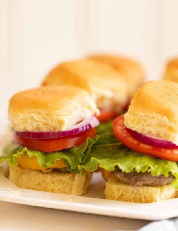 Platter with mini sliders, stacked with onion lettuce and tomato. #sliders