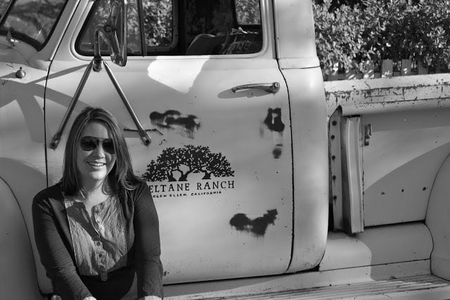 Julie posing in front of a white truck.