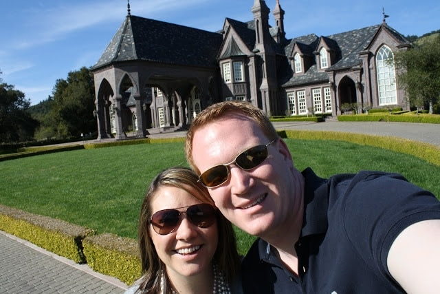 Julie and her husband taking a selfie in front of a dark brown house.