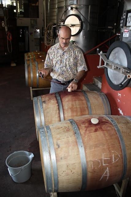 A man next to three barrels of wine.