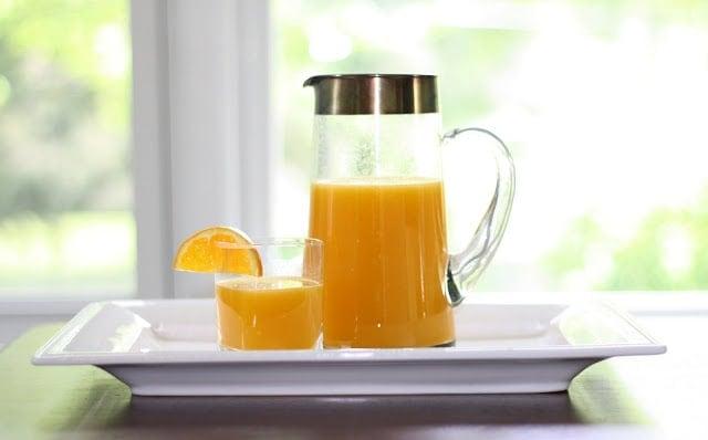 A glass pitcher of orange juice with a small glass of orange juice to the side, garnished with an orange slice.