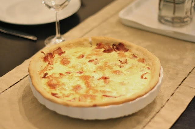 Quiche in a white pan on a wooden table.
