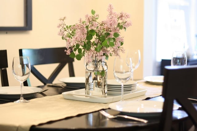 A set table with purple flowers in a mason jar as decoration.