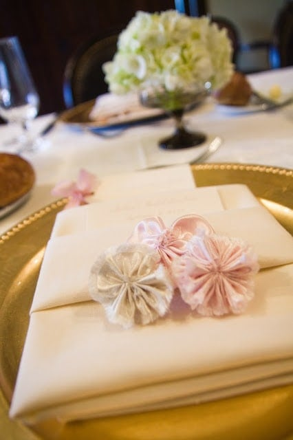 Napkins tied with fabric flowers.