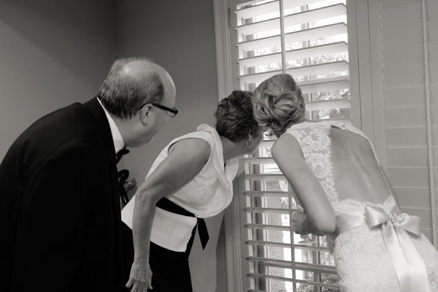 A Bride and her parents looking out the window.