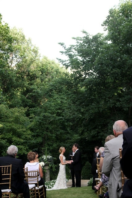 A group of people watching a man and a woman get married.