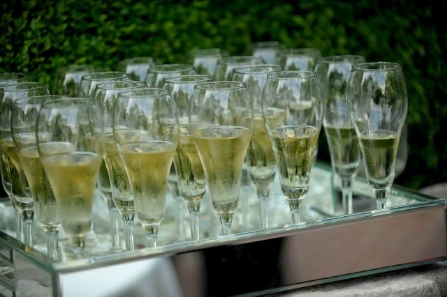 Glasses filled with white wine on a tray.