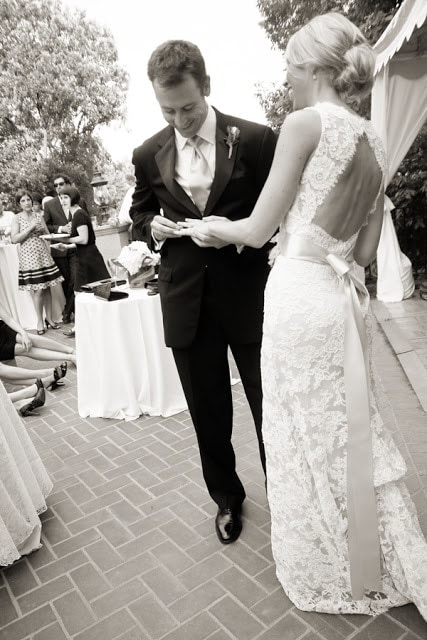 The groom fixing the bride\'s ring.