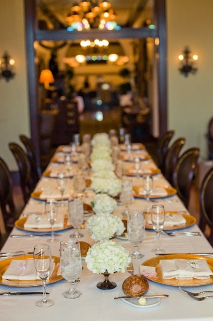 A Wedding dining table filled with white flower centerpieces.