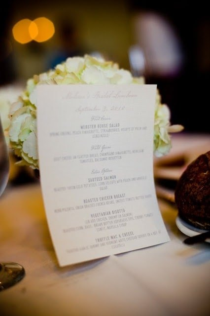 A food menu propped up with flowers.