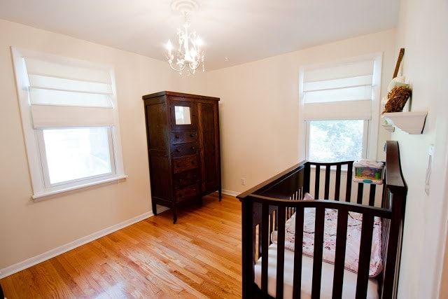 A babies room, with n armoire and a crib; both dark wood.