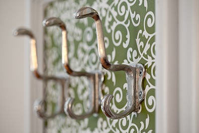 Wall hooks on green, patterned wall paper.