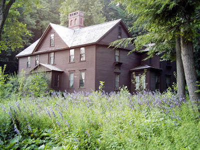 A brown house surrounded by trees and various shrubs and flowers.