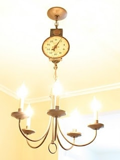 A chandelier with a vintage food scale at the top.