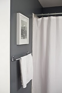 A bathroom with a white shower curtain, white towel, a picture of a mountain, and gray walls.