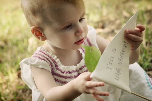 A small child sitting in the grass, holding a book in one hand and a leaf in the other.