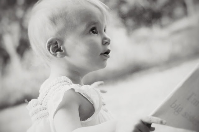 A small child looking off in the distance. The picture is in black and white.
