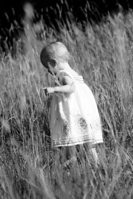A small child playing outside in the grass. The picture is in black and white.