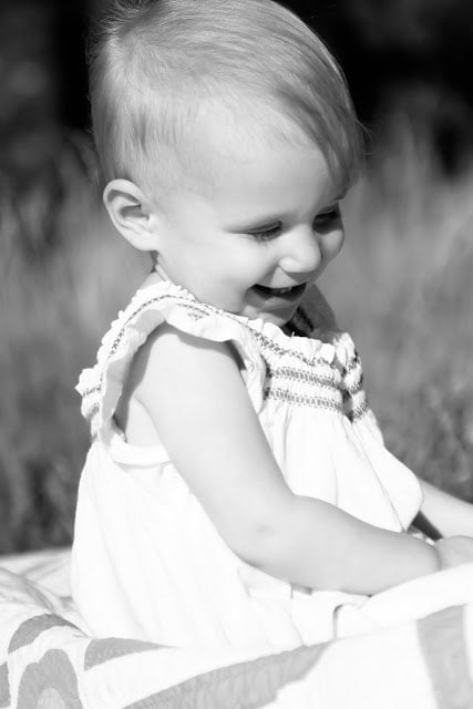 A small child outside sitting on a picnic blanket and laughing. The picture is in black and white.