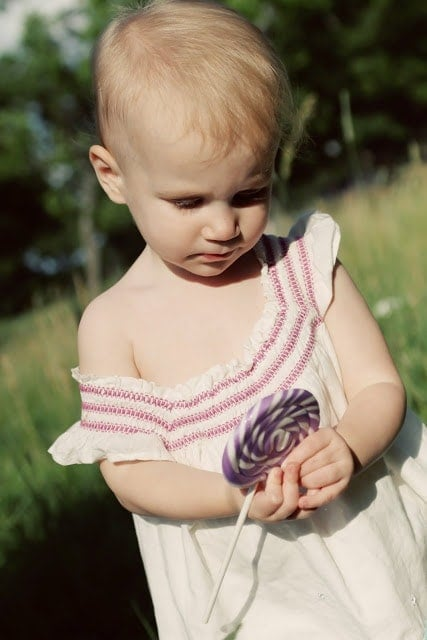 A small child playing outside while eating a purple and white striped lollipop.