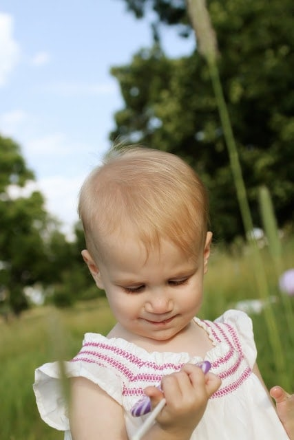 A small child playing outside in the grass.