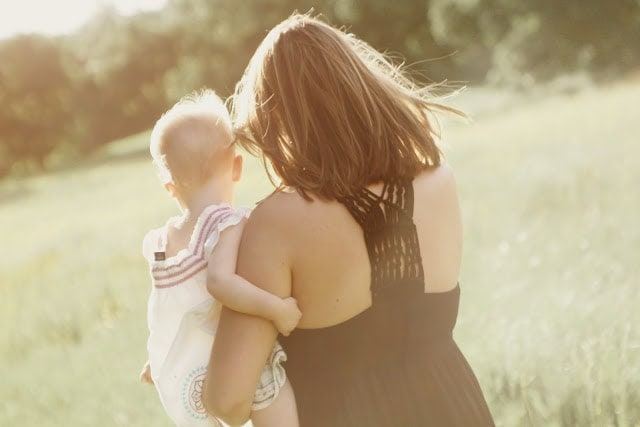A woman holding a small child outside with her wind blowing in the wind.
