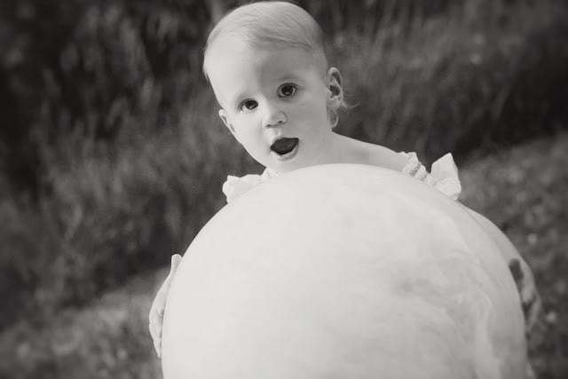 A small child playing outside with a large inflatable ball. The picture is in black and white.