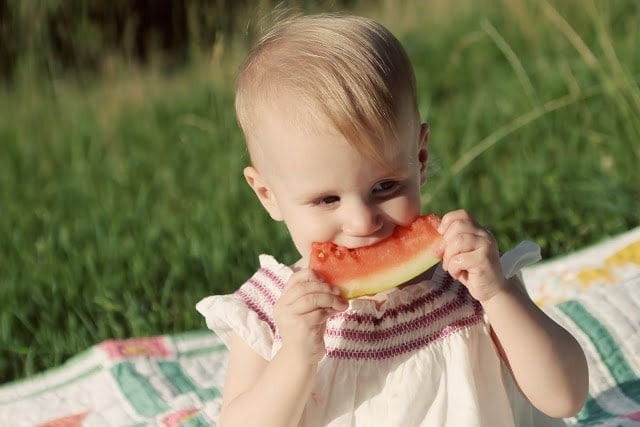 A baby eating a piece of watermelon on a picnic blanket outside.
