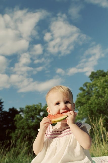 A baby eating a piece of watermelon outside, trees and sky in the background.