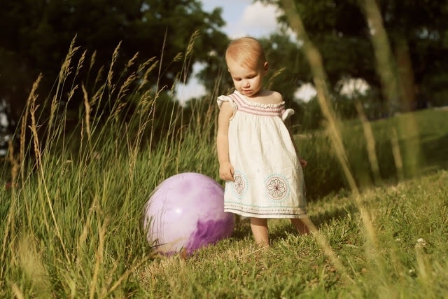 A small child playing outside with a large inflatable ball.