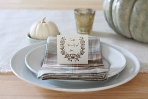 A fall table setting with rustic burlap runner and a plaid napkin on plate.