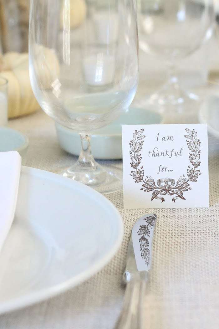 thankful for card next to plates, glassware on burlap