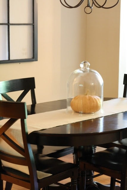 A pumpkin with a glass covering over it on a dining room table.
