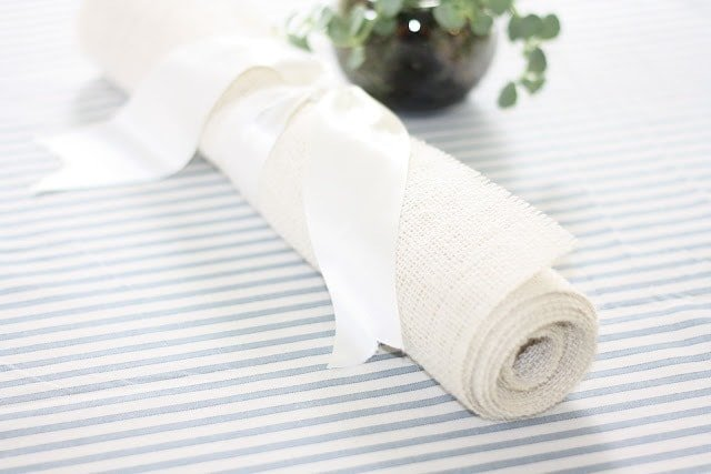Burlap table runner rolled up with ribbon to secure it