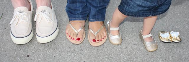 A woman\'s feet wearing flip flops and a little girls feet.
