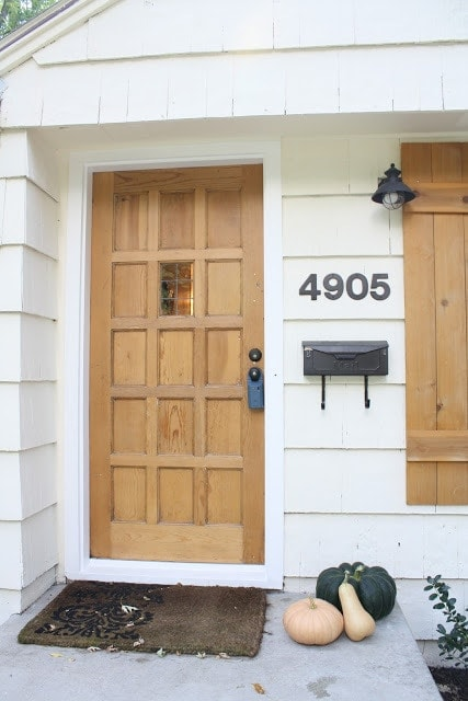 The front of a house, wooden doors and shutters.