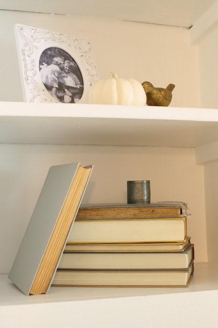 A small pumpkin on a white shelf with books.